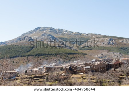 Smoking chimneys in the village of Valverde de los Arroyos, one of the Black Villages Guadalajara (Spain), with the Ocejon Peak in the background
