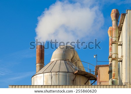 Smoking chimneys of a factory against a blue sky - stock photo