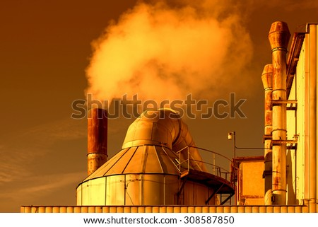 Smoking chimneys of a factory in the sunset - stock photo