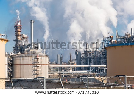 smoking chimneys of oil refinery in winter against a blue sky - stock photo