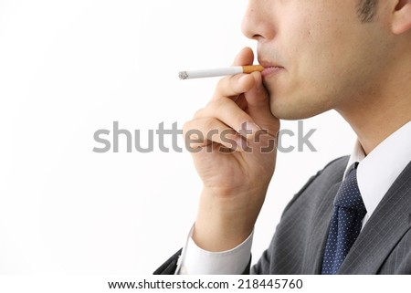 Smoking cigarette in silhouette studio isolated on white background - stock photo