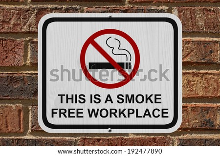 Smoking Free Workplace Sign, An red and white sign with cigarette icon and not symbol with text on a brick wall - stock photo