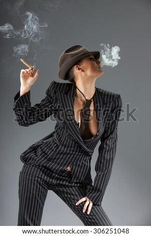 Smoking gangster women over gray background - stock photo