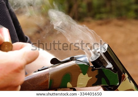 Smoking gun concept,  a double barreled over/under shotgun immediately after firing with shallow depth of field focused on the smoke leaving the breech - stock photo