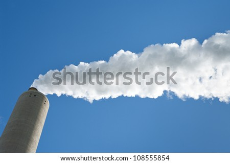 smoking industrial chimney against a blue sky - stock photo