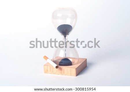 Smoking kills over time - hourglass and lies next to a cigarette. Time is up. Isolated white - stock photo