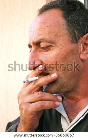 Smoking man vertical portrait. - stock photo