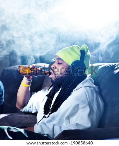 smoking marijuana and drinking beer amid clouds of smoke with copyspace - stock photo