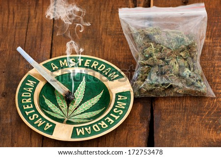 Smoking Marijuana Joint in an ashtray with amsterdam sign  and a big plastic bag of weed on wooden background - stock photo