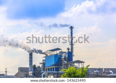 smoking of three chimneys from a factory against a blue sky - stock photo