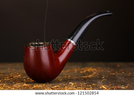 Smoking pipe and tobacco on wooden table on black background - stock photo