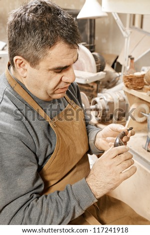 Smoking pipe maker examining finished work in workshop - stock photo