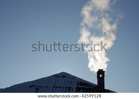 Smoking pipe on a snowy roof in a cold winter day - stock photo