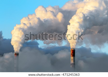 Smoking pipes of hydroelectric power station against the winter sky during a solar decline, Siberia, Russia