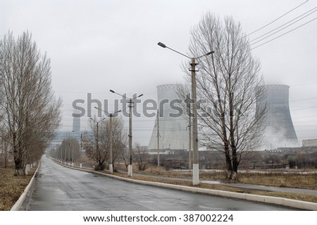 Smoking pipes of thermal power plant against a foggy sky - stock photo