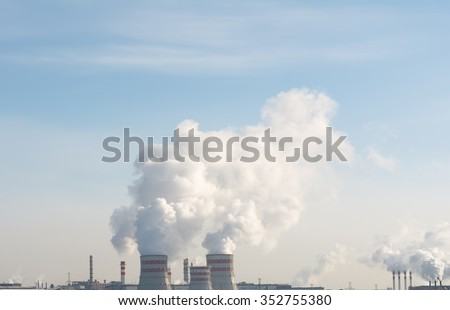 Smoking pipes of thermal power plant against blue sky ecology - stock photo