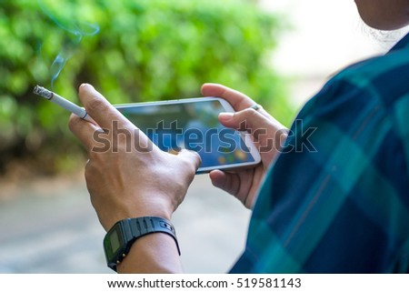 Smoking playing phone (Focus on left hand)
