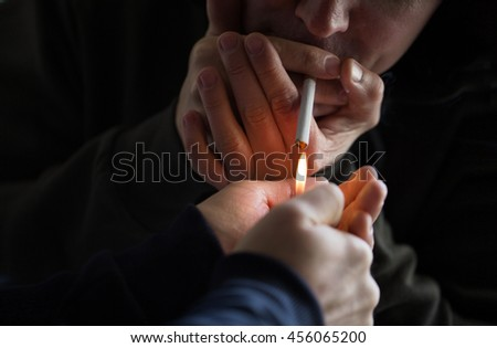 smoking, substance abuse, addiction and bad habits concept - close up of young people lighting cigarette outdoors - stock photo