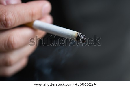 smoking, substance abuse, addiction, people and bad habits concept - close up of male hand with cigarette - stock photo