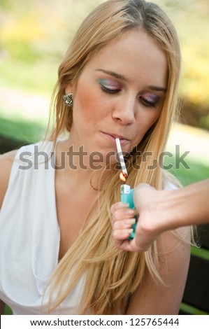 Smoking teenager - lighting cigarette - stock photo