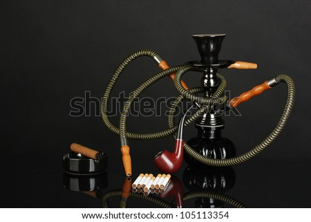 Smoking tools - a hookah, cigar, cigarette and pipe isolated on black background - stock photo