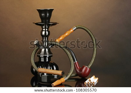 Smoking tools - a hookah, cigar, cigarette and pipe on brown background - stock photo