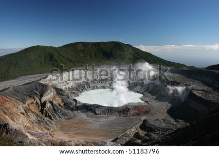 Smoking volcano in Costa Rica with blue sky - stock photo