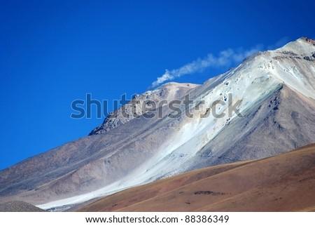 Smoking Volcano in in the desert of Bolivia - stock photo