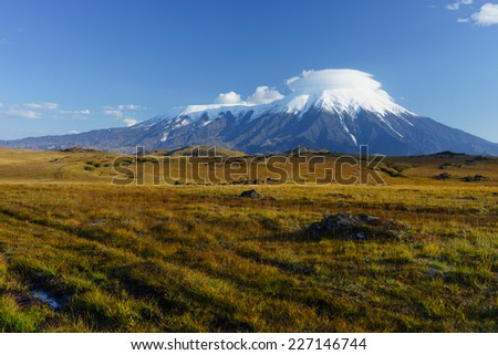 Smoking volcano in Kamchatka. Bezymyanny volcano smoking. Tundra in Kamchatka in autumn. - stock photo