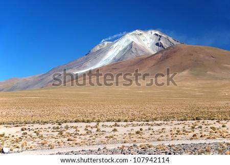 smoking volcano in the bolivian chilean atacama desert - stock photo