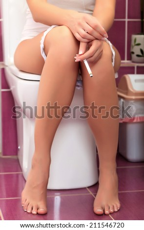 Smoking woman in a toilet - stock photo