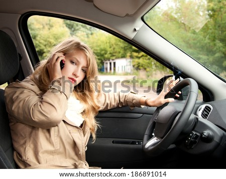 smoking young businesswoman  driving a car and speaking on the phone - stock photo