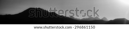 Smoky black and white silhouette of Mammoth Mountain, the Minarets, Mount Banner, and Mount Ritter in the Sierra Nevada Mountains - stock photo
