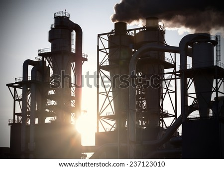 Smoky chimneys silhouettes against sun. Air pollution concept. - stock photo
