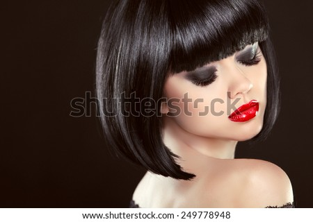 Smoky eyes makeup closeup. Black bob hairstyle. Sexy red lips. Brunette girl with shiny glossy short hair over dark background. - stock photo