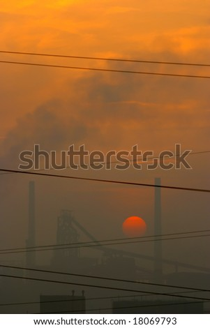 smoky factory at sunset - stock photo