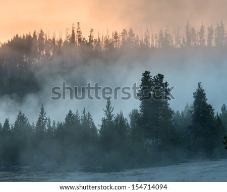 Smoky forest fire haze mixed with geyser steam at sunrise in Yellowstone National Park, Wyoming - stock photo
