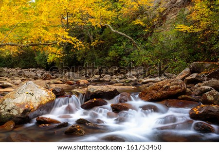 Smoky mountains stream, long exposure with fall colors in the distance - stock photo