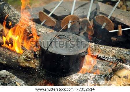 Smoky tourist kettle on fire background and grilled bread - stock photo