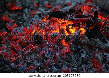 Smoldering ashes of a bonfire. - stock photo