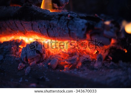smoldering bonfire with tongues of flame and embers on grass