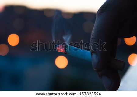 Smoldering cigarette in hand - stock photo
