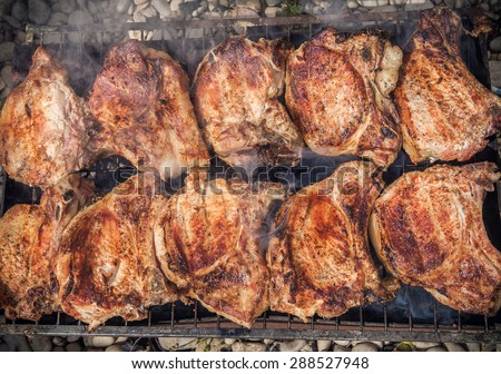 Smoldering juicy pork steaks grilling on the barbecue - stock photo