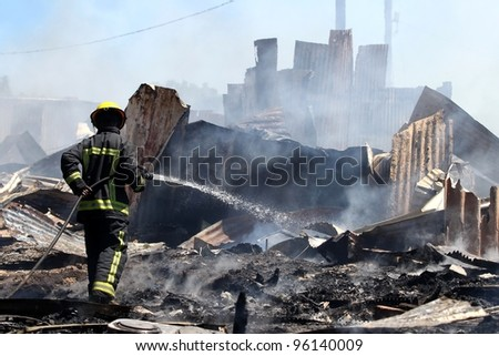 Smoldering remains of a ghetto house with a fireman spraying water