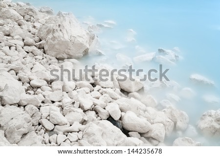 Smooth blue waves breaking on white chalk stone coast. Long exposure with blurred motion. - stock photo