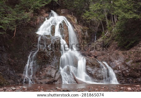 Smooth flowing  waterfall in forested area. - stock photo