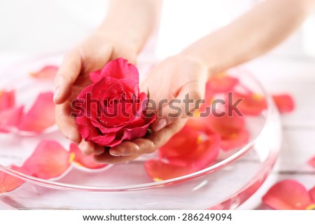 Smooth leather palm, beauty treatment clinic. Care treatment of hands and nails woman hands over the bowl with rose petals  - stock photo