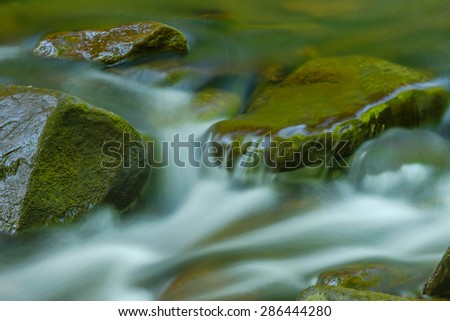 Smooth moss covered stones with flowing water in a clear spring brook - stock photo