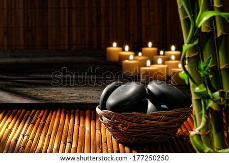 Smooth polished black hot massage stones in a basket with candles and bamboo stems in relaxing Zen inspired soothing atmosphere of wellness holistic spa for a natural well-being rejuvenation session  - stock photo
