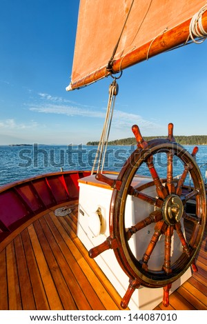 Smooth sailing on a classic schooner with a close view of the captain's wheel. Colorful image with a bright blue sky, an orange sail and wood decking. - stock photo
